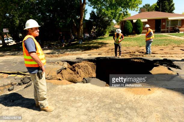 Denver water department officials look into a large sinkhole that Denver Fire Department ladder truck Tower 23 was stuck in for hours on Zuni street...