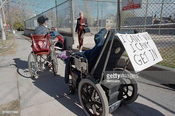 Wheelchair bound protesters surround an entrance to a Denver polling place to draw attention to the flights of stairs that make it impossible to them...