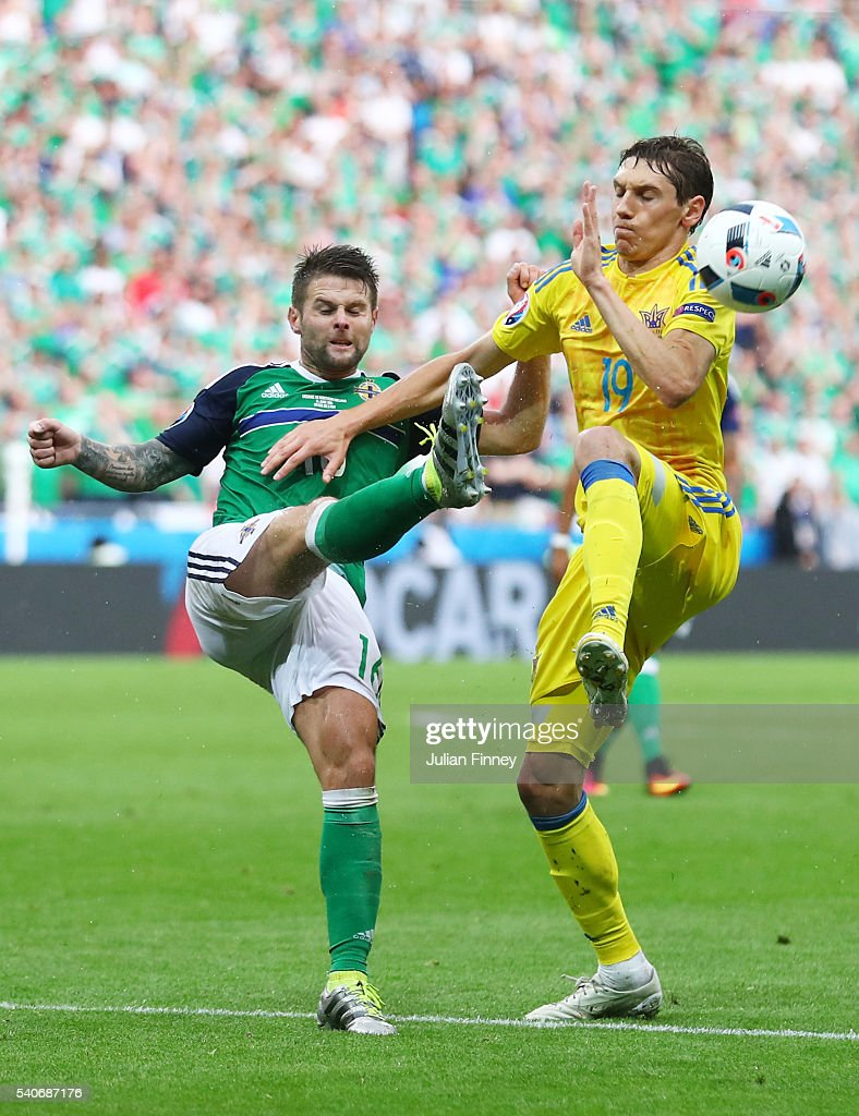 Denys Garmash of Ukraine and Oliver Norwood of Northern Ireland compete for the ball during the UEFA EURO 2016 Group C match between Ukraine and Northern Ireland at Stade des Lumieres on June 16, 2016 in Lyon, France.