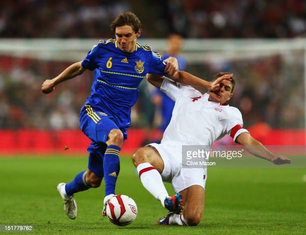 Denys Garmash of Ukraine holds off the challenge of Steven Gerrard of England during the FIFA 2014 World Cup Group H qualifying match between England...
