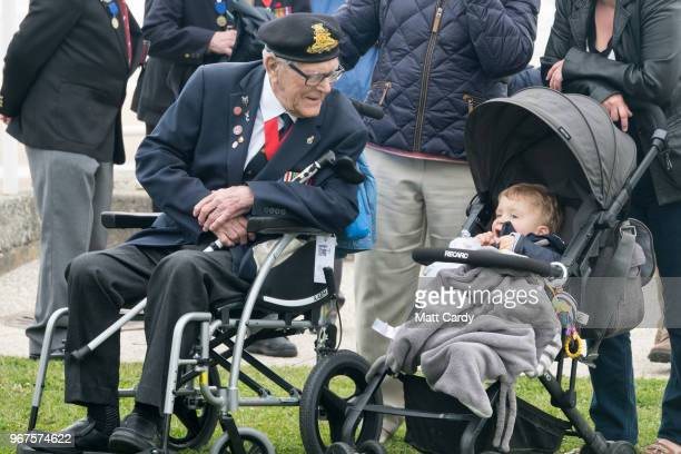 Denys Hunter who was in the Hertfordshire Yeomanry and landed on Gold Beach on DDay speaks with a young child as fellow Normandy veterans attend a...