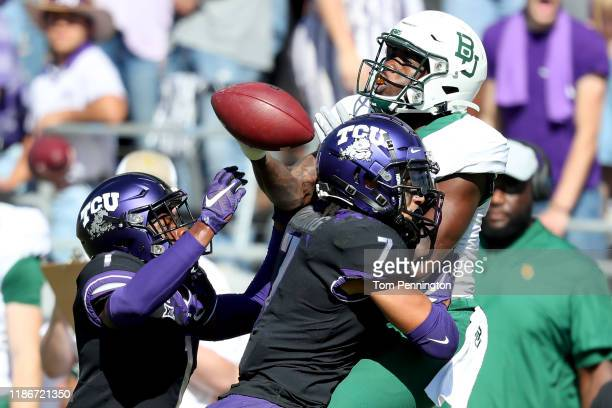 Denzel Mims of the Baylor Bears bobbles a pass against Tre'Vius HodgesTomlinson of the TCU Horned Frogs and Trevon Moehrig of the TCU Horned Frogs in...