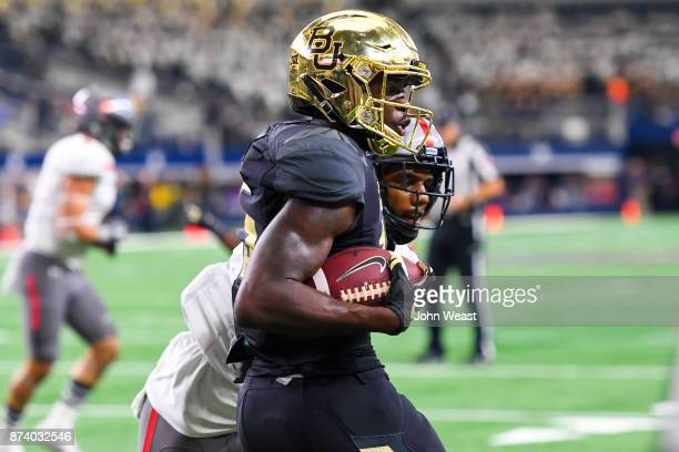 Denzel Mims of the Baylor Bears catches a pass and scores touchdown while being defended by Jaylon Lane of the Texas Tech Red Raiders during the game...