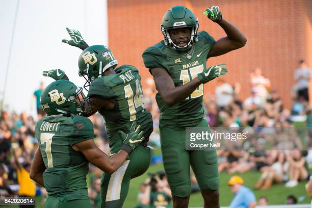Denzel Mims of the Baylor Bears celebrates after scoring a touchdown on a 45 yard touchdown reception with teammates Chris Platt and John Lovett...