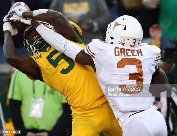 Denzel Mims of the Baylor Bears drops a pass while defended by Jalen Green of the Texas Longhorns in the second half at McLane Stadium on November 23...