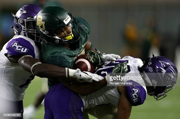 Denzel Mims of the Baylor Bears makes a pass reception against Bolu Onifade and Koy Richardson of the Abilene Christian Wildcats at McLane Stadium on...