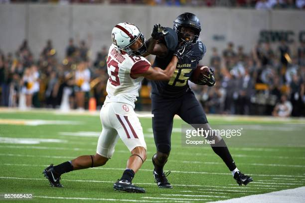 Denzel Mims of the Baylor Bears stiff arms Tre Norwood of the Oklahoma Sooners during the second half at McLane Stadium on September 23 2017 in Waco...