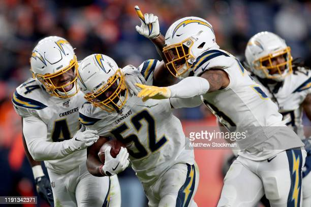 Denzel Perryman of the Los Angeles Chargers celebrates with Kyzir White and Derwin James after making an interception against the Denver Broncos in...