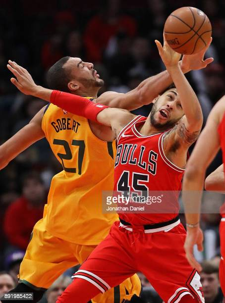 Denzel Valentine of the Chicago Bulls and Rudy Gobert of the Utah Jazz battle for a rebound at the United Center on December 13 2017 in Chicago...