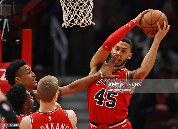 Denzel Valentine of the Chicago Bulls as John Collins of the Atlanta Hawks gets a hand in his face at the United Center on October 26 2017 in Chicago...