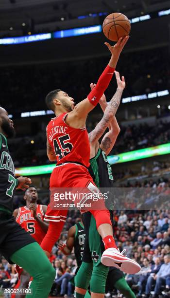Denzel Valentine of the Chicago Bulls puts up a shot over Daniel Theis of the Boston Celtics at the United Center on December 11 2017 in Chicago...