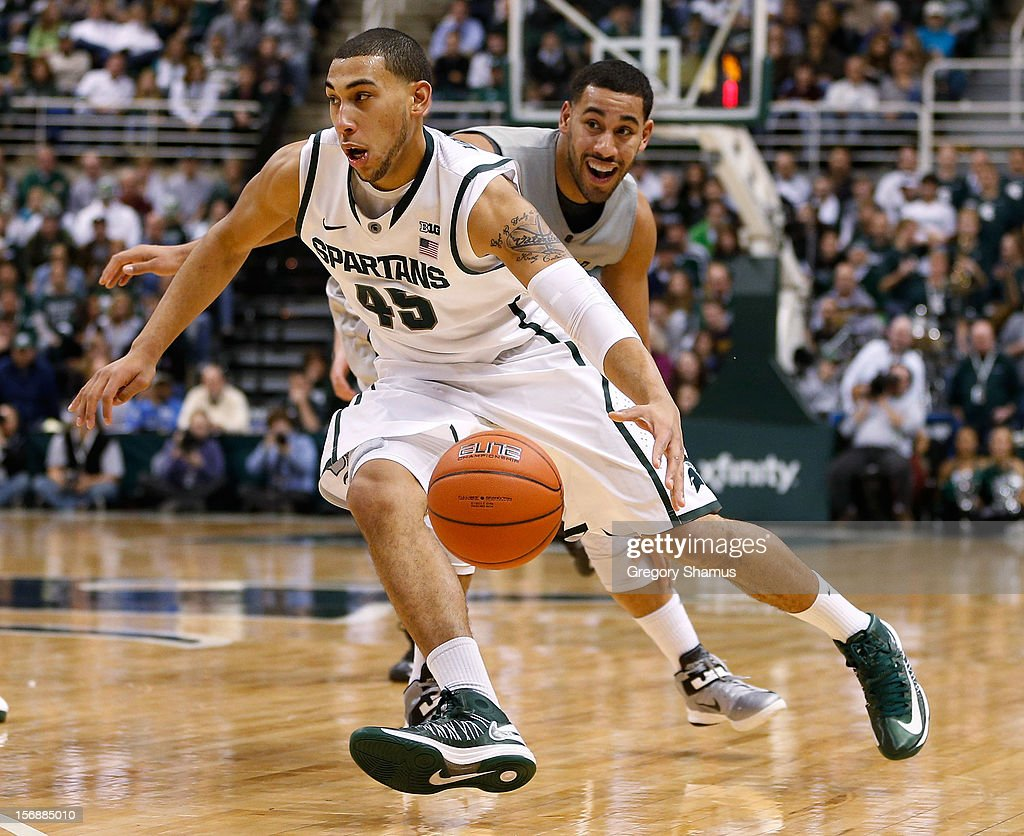 Denzel Valentine #45 of the Michigan State Spartans controls the ball after getting around Raphael Carter #21 of the Oakland Golden Grizzlies at the Jack T. Breslin Students Events Center on November 23, 2012 in East Lansing, Michigan. Michigan State won the game 70-52.