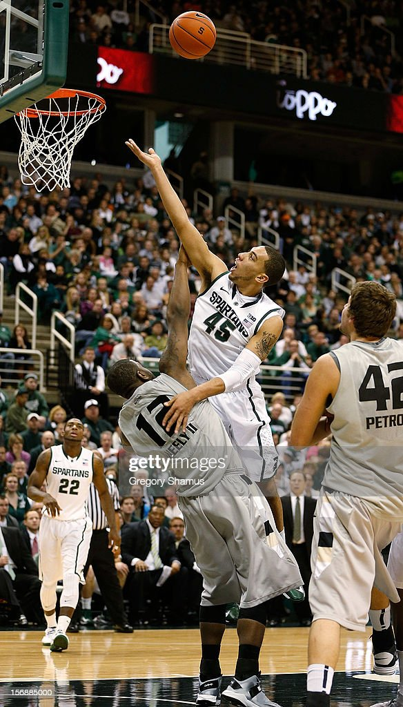 Denzel Valentine #45 of the Michigan State Spartans gets a second half shot off over Lloyd Neely II #12 of the Oakland Golden Grizzlies at the Jack T. Breslin Students Events Center on November 23, 2012 in East Lansing, Michigan. Michigan State won the game 70-52.