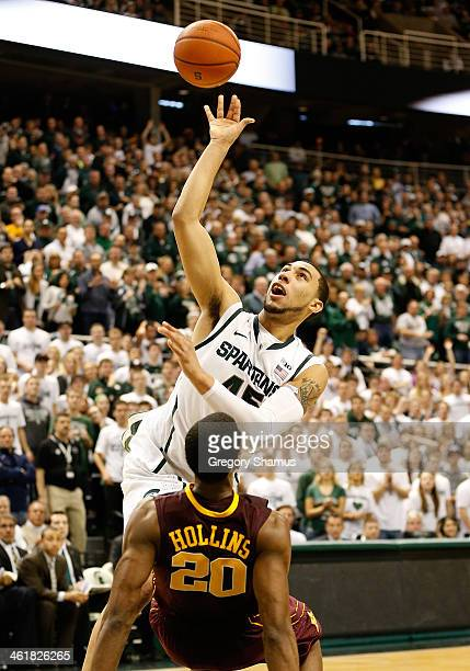 Denzel Valentine of the Michigan State Spartans gets a second half shot off over Austin Hollins of the Minnesota Golden Gophers at the Jack T Breslin...