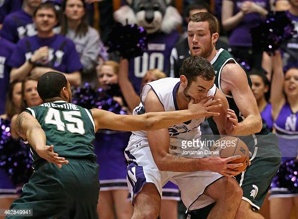 Denzel Valentine of the Michigan State Spartans gets his hand in the face of Alex Olah of the Northwestern Wildcats as he tries to move past Matt...