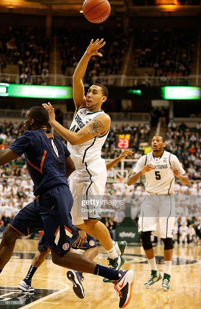 Denzel Valentine #45 of the Michigan State Spartans reaches for the ball against Sam McLaurin #0 of the Illinois Fighting Illini at the Jack T. Breslin Student Events Center on January 31, 2013 in East Lansing, Michigan.