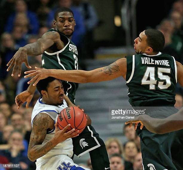 Denzel Valentine of the Michigan State Spartans smacks James Young of the Kentucky Wildcats in the head as Branden Dawson defends during the State...
