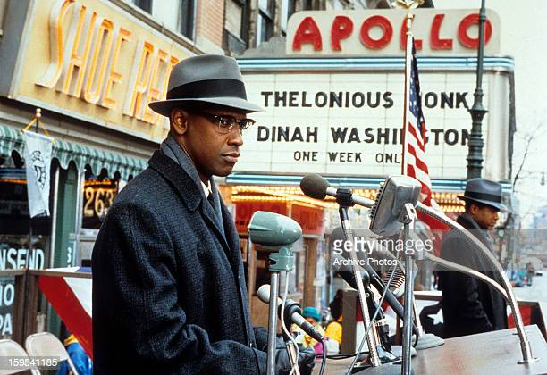 Denzel Washington standing behind microphones on the city street in a scene from the film 'Malcom X' 1992