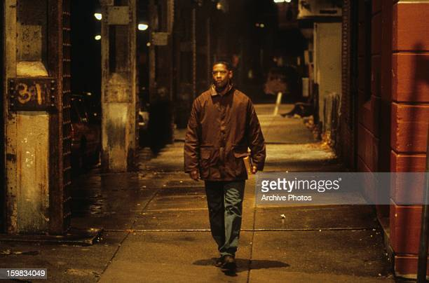 Denzel Washington walking down dark sidewalk in a scene from the film 'Fallen' 1998