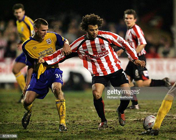 Deon Burton of Brentford holds off Calum Davenport of Southampton during The FA Cup fifth Round replay match between Brentford and Southampton held...
