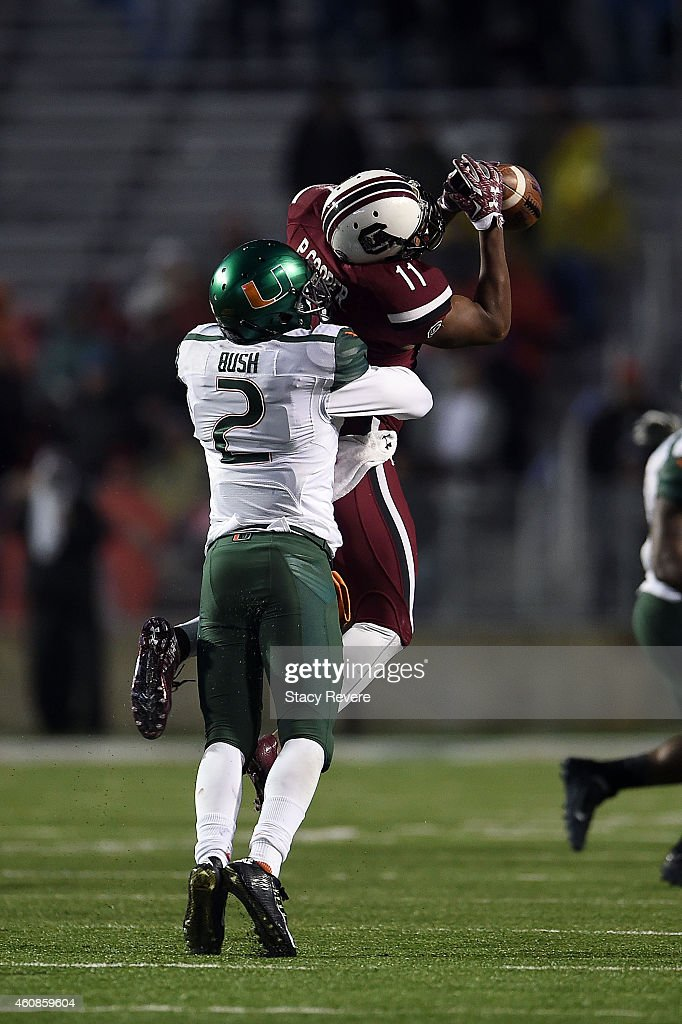 Deon Bush #2 of the Miami Hurricanes hits Pharoh Cooper #11 of the South Carolina Gamecocks to dislodge the ball during the third quarter of the Duck Commander Independence Bowl at Independence Stadium on December 27, 2014 in Shreveport, Louisiana.
