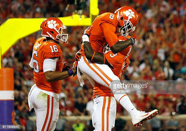 Deon Cain of the Clemson Tigers is congratulated by his teammates Jordan Leggett and Artavis Scott after scoring a second quarter touchdown reception...