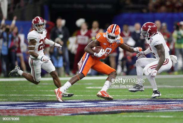 Deon Cain of the Clemson Tigers runs with the ball as Tony Brown of the Alabama Crimson Tide and Anthony Averett defend in the first half of the...