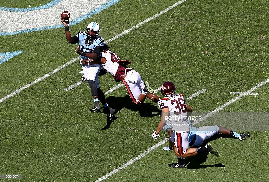 Deon Clarke #40 of the Virginia Tech Hokies hits Marquise Williams #12 of the North Carolina Tar Heels during their game at Kenan Stadium on October 4, 2014 in Chapel Hill, North Carolina.