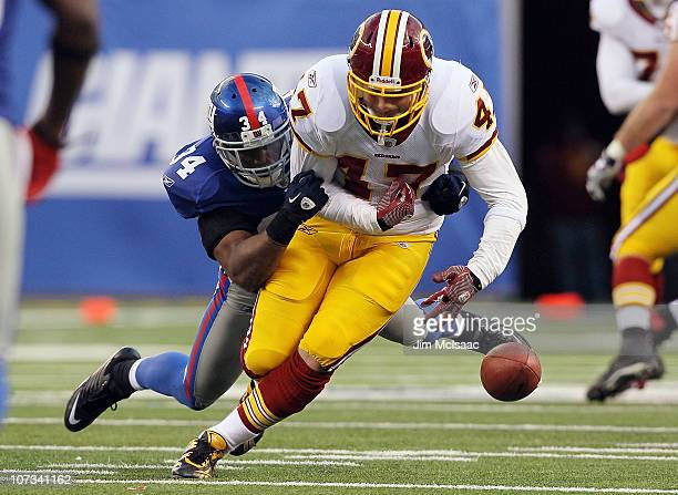 Deon Grant of the New York Giants forces a fourth quarter fumble against Chris Cooley of the Washington Redskins on December 5 2010 at the New...