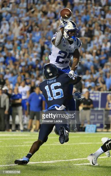 Deon Jackson of the Duke Blue Devils throws an interception as DJ Ford of the North Carolina Tar Heels tries to stop him late in the fourth quarter...