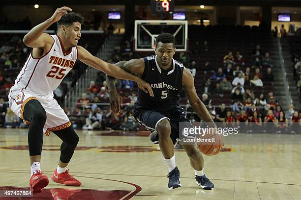 Deon Jones of the Monmouth Hawks brings the ball up court against Bennie Boatwright of the USC Trojans at Galen Center on November 16 2015 in Los...