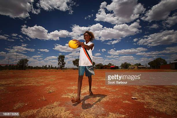Deon Lechleitner kicks an Australian Rules football as members of the Indigenous All Stars visit Yuendumu School in the Australian outback ahead of...
