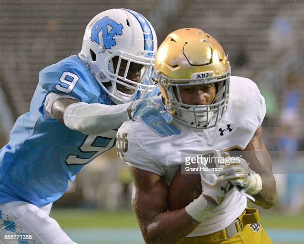 Deon McIntosh of the Notre Dame Fighting Irish breaks away from KJ Sails of the North Carolina Tar Heels fir a touchdown during the game at Kenan...