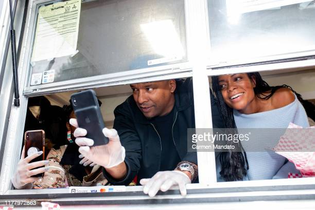 Deon Taylor and Naomie Harris are seen serving from a food truck during the Black Blue cast members' visit to Morehouse College on October 24 2019 in...