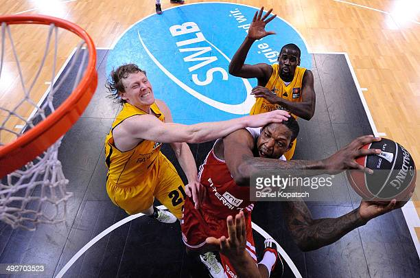Deon Thompson of Muenchen is challenged by Coby Karl of Ludwigsburg during the Beko BBL Playoffs semifinal match between MHP RIESEN Ludwigsburg and...