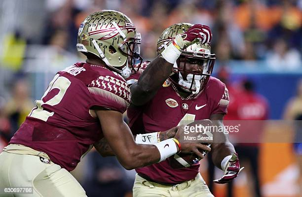 Deondre Francois fakes a hand off to Dalvin Cook of the Florida State Seminoles in the first half against the Michigan Wolverines during the Capitol...