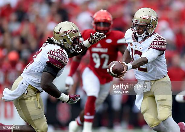 Deondre Francois of the Florida State Seminoles hands off the ball to Dalvin Cook during the game against the Louisville Cardinals at Papa John's...