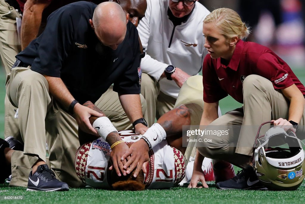 Deondre Francois #12 of the Florida State Seminoles is attended to by medical personnel after being injured in the fourth quarter of their game against the Alabama Crimson Tide at Mercedes-Benz Stadium on September 2, 2017 in Atlanta, Georgia.