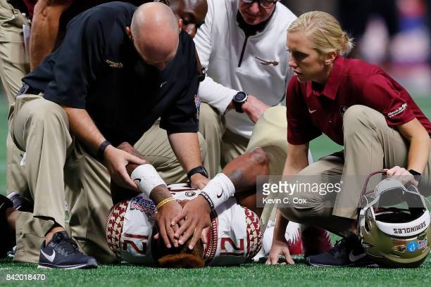 Deondre Francois of the Florida State Seminoles is attended to by medical personnel after being injured in the fourth quarter of their game against...