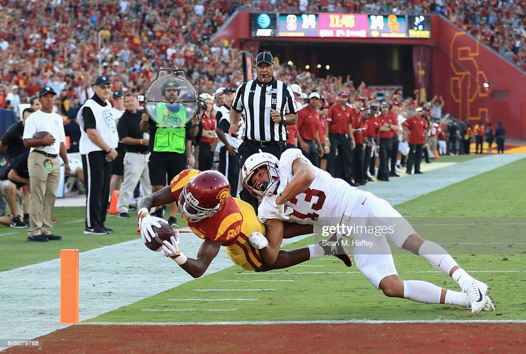 Deontay Burnett #80 of the USC Trojans dives into the end zone to score a second quarter touchdown as Alijah Holder #13 of the Stanford Cardinal attempts to tackle him at Los Angeles Memorial Coliseum on September 9, 2017 in Los Angeles, California.