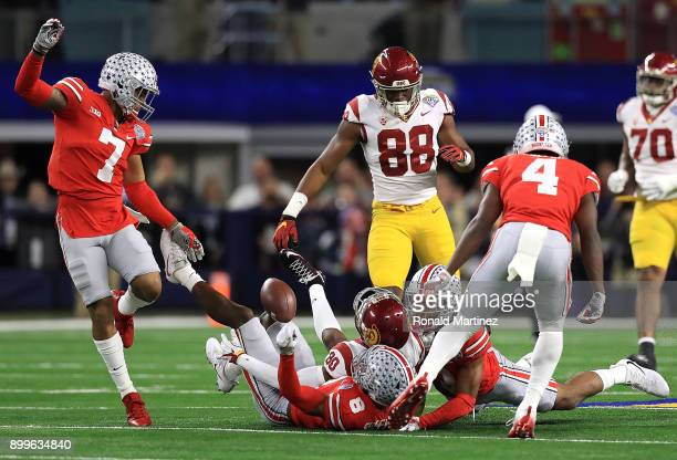 Deontay Burnett of the USC Trojans fumbles the ball while tackled by Damon Arnette and Kendall Sheffield of the Ohio State Buckeyes in the first...