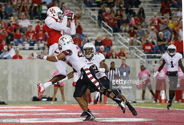 Deontay Greenberry of the Houston Cougars leaps for a 7yard touchdown in the third quater over Alex Wells and Will Hayes of the Temple Owls during...