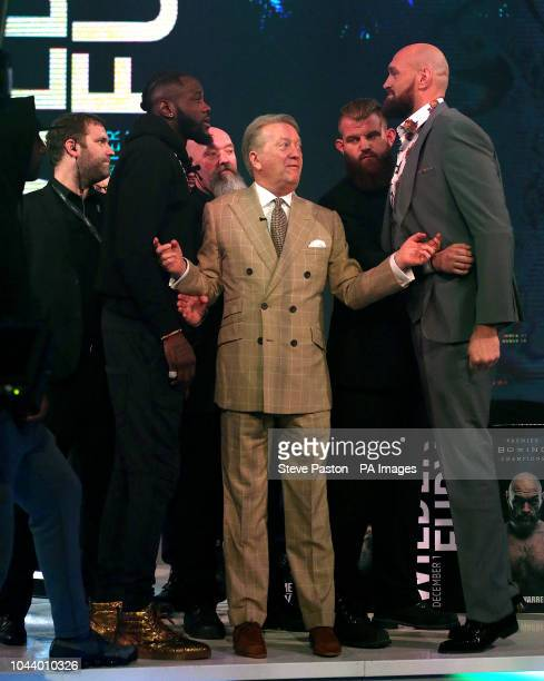 Deontay Wilder and Tyson Fury react as promoter Frank Warren keeps them apart during a press conference at BT Sport Studio London