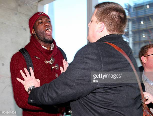 Deontay Wilder is held back as he argues with Artur Szpilka during a portrait and media availability on the terrace at Four World Trade Center on...
