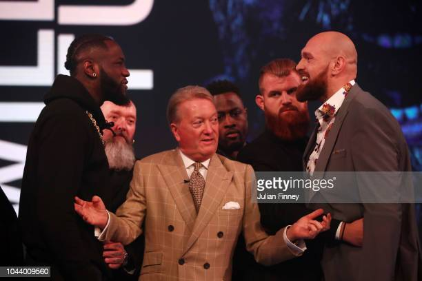 Deontay Wilder of United States and Tyson Fury of England reacts during a face off as promoter Frank Warren keeps them apart during a press...