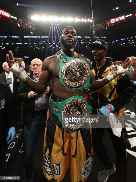 Deontay Wilder poses with trainer Marc Breland after knocking out Luis Ortiz in the tenth round of their WBC Heavyweight Championship fight at...