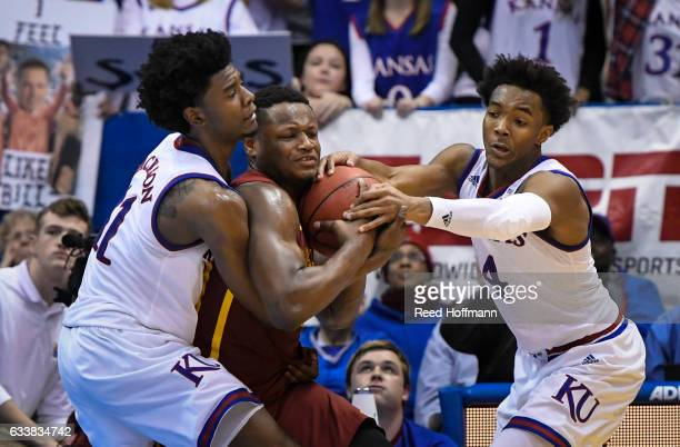 Deonte Burton of the Iowa State Cyclones holds on to the ball while being pressured by Josh Jackson of the Kansas Jayhawks and Devonte' Graham of the...