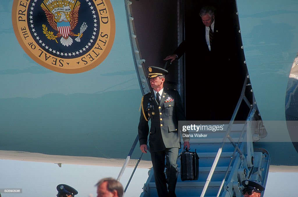 Dep. NSC Adviser Bob Gates de- planing, w. football carrier (mil. aide w. briefcase-carried nuclear missile launch code), in fore, (w. campaigning Pres. Bush) in CA.