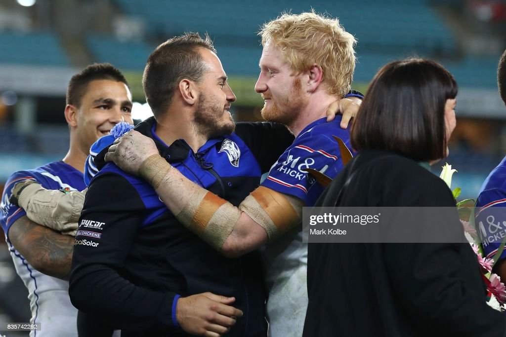 Departing Bulldogs player Josh Reynolds embraces James Graham of the Bulldogs on stage after a presentation to the players and officials leaving the club at the end of the season after the round 24 NRL match between the Canterbury Bulldogs and the Manly Sea Eagles at ANZ Stadium on August 20, 2017 in Sydney, Australia.