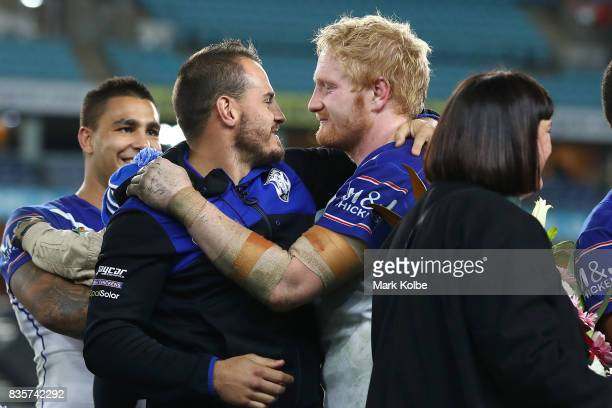 Departing Bulldogs player Josh Reynolds embraces James Graham of the Bulldogs on stage after a presentation to the players and officials leaving the...
